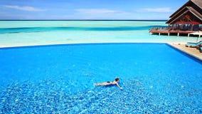 Woman swimming across infinity blue pool in tropics stock video footage