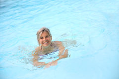 Woman swimming in blue pool Stock Image