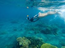 Woman swimming in blue sea. Snorkeling girl in full-face snorkeling mask. Royalty Free Stock Images