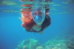 Woman swimming in blue sea. Snorkeling woman in full face mask. Stock Photo