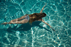 Woman swimming on a blue water pool Royalty Free Stock Photography