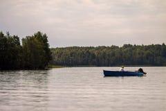 Woman swimming in boat. On lake in northen Karelia Stock Photo