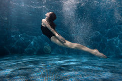 Woman is swimming at the bottom of the pool. Stock Image
