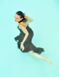 Woman swimming in dress. Aerial view of middle aged woman wearing formal dress swimming in pool Royalty Free Stock Photo