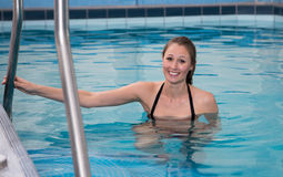 Woman swimming forward crawl in public swimming pool Royalty Free Stock Images