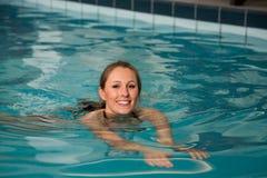 Woman swimming forward crawl in public swimming pool Royalty Free Stock Image