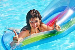 Woman swimming on inflatable beach mattress. Stock Photo