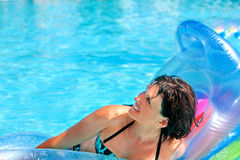 Woman swimming on inflatable beach mattress Royalty Free Stock Images