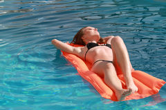 Woman swimming on inflatable mattress Royalty Free Stock Images
