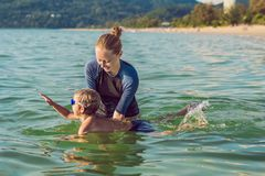 Woman swimming instructor for children is teaching a happy boy to swim in the sea royalty free stock image