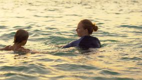 Woman swimming instructor teaches little boy swimming in a sea during a sundet.  stock footage
