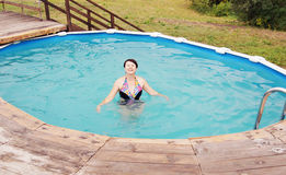 Woman is swimming in a little outdoor pool Royalty Free Stock Images