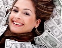 Woman swimming in money Royalty Free Stock Photography