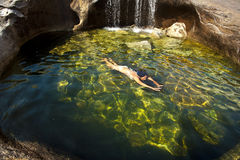 Woman swimming in a natural pool. Royalty Free Stock Image