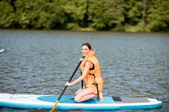Woman swimming on the paddleboard. Woman in life vest learning to swim with oar on the standup paddleboard on the lake Royalty Free Stock Photo