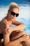 Woman by a swimming pool. Portrait of a beautiful woman in the sunglasses by a swimming pool Stock Photo