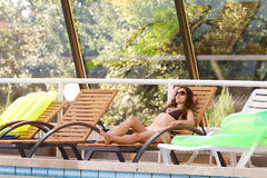 Woman by the swimming pool. Shot of woman relaxing by the swimming pool Royalty Free Stock Photo
