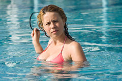 Woman in the swimming pool. Beautiful young woman holding a pair of sun glasses in the swimming pool Royalty Free Stock Images