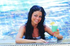 Woman in swimming pool with cocktail royalty free stock photos