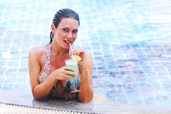 Woman in swimming pool with cocktail Stock Photography