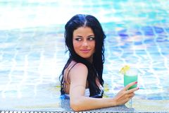 Woman in swimming pool with cocktail Royalty Free Stock Image