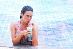 Woman in swimming pool with cocktail Royalty Free Stock Images
