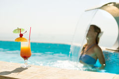Woman in swimming pool. Woman in the swimming pool with cocktail Stock Photos