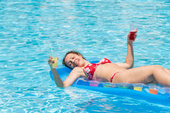 Woman swimming in the pool on an inflatable mattress Royalty Free Stock Photo