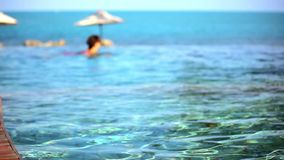 Woman swimming in pool and ocean at the. *oman swimming in the pool and ocean in the background. Video shift motion 1920*1080 stock video footage