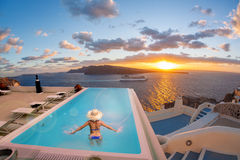 Woman in the swimming pool in Oia village on Santorini island, Greece. Woman in the swimming pool against sunset in Oia village on Santorini island, Greece Stock Photography