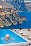 Woman in the swimming pool, Oia village on Santorini island, Greece Royalty Free Stock Image