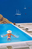 Woman in the swimming pool, Oia village on Santorini island, Greece Royalty Free Stock Photos