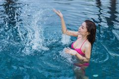 Woman in pool and playing water splash. Woman in swimming pool and playing water splash Stock Images