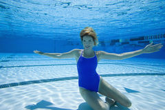 Woman in swimming pool, portrait, underwater view stock images