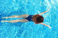 Woman swimming in pool. Top view. Straight body, slim. Breaststroke swimmer. royalty free stock images