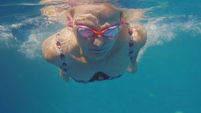 A woman is swimming in the pool. Underwater video stock video footage