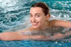 Woman in the swimming pool. Young woman enjoying jacuzzi in the swimming pool at the hotel spa stock image