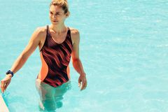 Woman in swimming pool. Young woman in swimsuit walking the wading pool. Female in swimwear in the swimming pool royalty free stock photo
