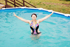 Woman is swimming in a small outdoor pool Stock Photography