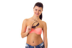 Woman in swimming suit, shorts and sunglasses. Happy young woman with long ponytail in pink bra and denim shorts with black sunglasses on white background in Stock Photos
