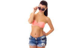 Woman in swimming suit, shorts and sunglasses. Young adorable woman with long ponytail in pink bra and denim shorts with black sunglasses on white background in Stock Photo