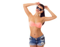 Woman in swimming suit, shorts and sunglasses. Young beautiful woman with long ponytail in pink bra and denim shorts with black sunglasses on white background in Stock Photography