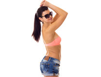 Woman in swimming suit, shorts and sunglasses. Young nice woman with long ponytail in pink bra and denim shorts with black sunglasses on white background in Stock Image