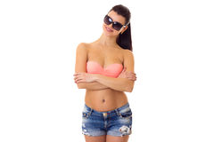 Woman in swimming suit, shorts and sunglasses. Young optimistic woman with long ponytail in pink bra and denim shorts with black sunglasses on white background Royalty Free Stock Photography