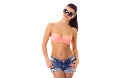 Woman in swimming suit, shorts and sunglasses. Young pleasant woman with long ponytail in pink bra and denim shorts with black sunglasses on white background in Royalty Free Stock Images