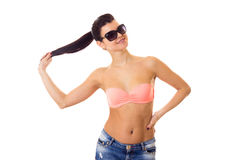 Woman in swimming suit, shorts and sunglasses. Young positive woman with long ponytail in pink bra and denim shorts with black sunglasses on white background in Stock Photos