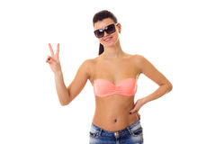 Woman in swimming suit, shorts and sunglasses. Young smiling woman with long ponytail in pink bra and denim shorts with black sunglasses showing PEACE on white Royalty Free Stock Images