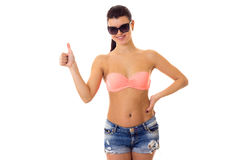 Woman in swimming suit, shorts and sunglasses. Young smiling woman with long ponytail in pink bra and denim shorts with black sunglasses showing thumb up on Stock Images