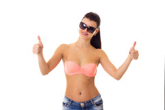 Woman in swimming suit, shorts and sunglasses. Young smiling woman with long ponytail in pink bra and denim shorts with black sunglasses showing thumbs up on Stock Photography