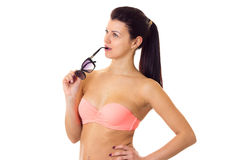 Woman in swimming suit with sunglasses. Beautiful young woman with long ponytail in pink bra and denim shorts with black sunglasses on white background in studio Royalty Free Stock Photo